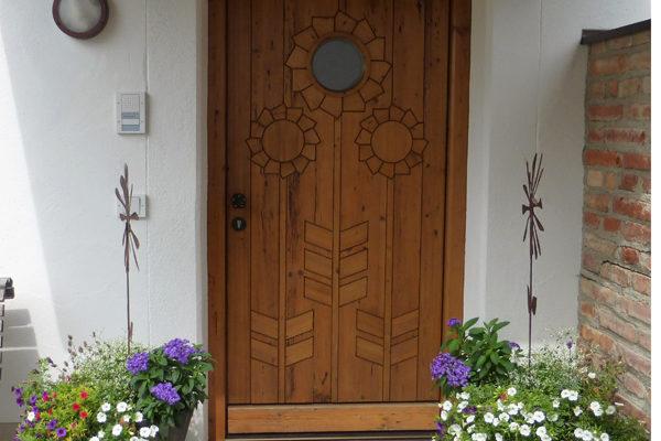 Haustüre mit Sonnenblumen und Fenster